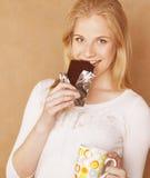 Muchacha rubia linda joven que come el chocolate y que bebe ascendente cercano del café Fotografía de archivo
