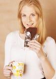 Muchacha rubia linda joven que come el chocolate y que bebe ascendente cercano del café Fotos de archivo libres de regalías