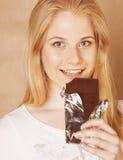 Muchacha rubia linda joven que come el chocolate y que bebe ascendente cercano del café Fotografía de archivo libre de regalías