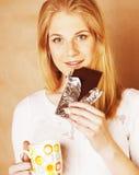 Muchacha rubia linda joven que come el chocolate y que bebe cierre del café Fotos de archivo