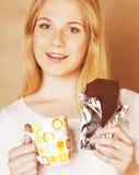 Muchacha rubia linda joven que come el chocolate y que bebe cierre del café Imagenes de archivo