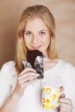 Muchacha rubia linda joven que come el chocolate y que bebe cierre del café Foto de archivo libre de regalías