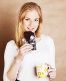 Muchacha rubia linda joven que come el chocolate y que bebe cierre del café Foto de archivo