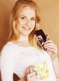 Muchacha rubia linda joven que come el chocolate y que bebe cierre del café Imagen de archivo libre de regalías