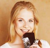 Muchacha rubia linda joven que come el chocolate y que bebe cierre del café Imagen de archivo