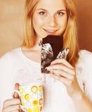 Muchacha rubia linda joven que come el chocolate y que bebe cierre del café Imágenes de archivo libres de regalías