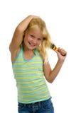 Muchacha rubia linda que aplica su pelo con brocha Fotografía de archivo libre de regalías