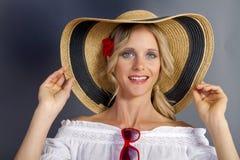 Muchacha rubia linda que desgasta un sombrero del verano de la paja imagen de archivo