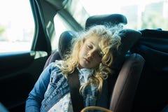 Muchacha rubia linda que duerme en un asiento de carro Fotos de archivo