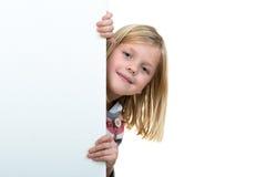 Muchacha rubia linda que lleva a cabo una muestra en blanco Fotografía de archivo libre de regalías