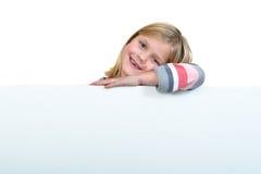 Muchacha rubia linda que lleva a cabo una muestra en blanco Foto de archivo libre de regalías