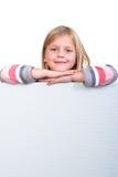 Muchacha rubia linda que lleva a cabo una muestra en blanco Imágenes de archivo libres de regalías