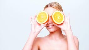 Muchacha rubia linda que sostiene la fruta anaranjada almacen de metraje de vídeo
