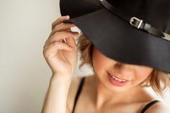 Muchacha rubia muy atractiva, adentro con el sombrero y la media, sentada en ambiente elegante Imagen de archivo