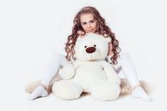Muchacha rubia oscura atractiva que se sienta con el oso de peluche Imagen de archivo