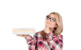 Muchacha rubia pensativa con los vidrios y los libros oh la mano Foto de archivo libre de regalías