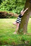 Muchacha rubia por el árbol Fotografía de archivo libre de regalías