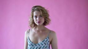Muchacha rubia positiva alegre que presenta para la cámara en un estudio de la foto en un fondo rosado almacen de video