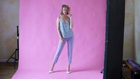 Muchacha rubia positiva alegre que presenta para la cámara en un estudio de la foto en un fondo rosado almacen de metraje de vídeo