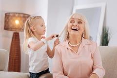 Muchacha rubia positiva que cepilla su pelo de las abuelas Foto de archivo