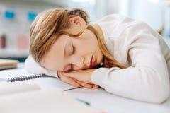 Muchacha rubia preciosa que duerme sobre su cuaderno foto de archivo libre de regalías