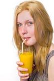 Muchacha rubia que bebe el zumo de naranja con la paja Foto de archivo