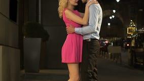 Muchacha rubia que da la mano al individuo, par que abraza en calle, relación del amor, fecha metrajes