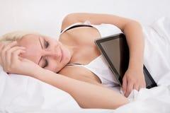 Muchacha rubia que duerme en la cama que sostiene una PC de la tableta Imágenes de archivo libres de regalías