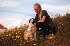 Muchacha rubia que juega con el mastín español del perrito en un campo de flores amarillas imagenes de archivo