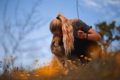 Muchacha rubia que juega con el mast?n espa?ol del perrito en un campo de flores amarillas fotos de archivo