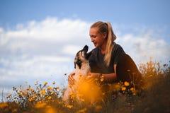 Muchacha rubia que juega con el mast?n espa?ol del perrito en un campo de flores amarillas imágenes de archivo libres de regalías