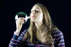 Muchacha rubia que juega con las burbujas de jabón Imagen de archivo