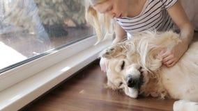 Muchacha rubia que juega con un perro almacen de metraje de vídeo