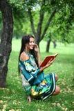 Muchacha rubia que lee un libro en el parque Fotografía de archivo