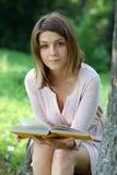 Muchacha rubia que lee un libro en el parque Imágenes de archivo libres de regalías