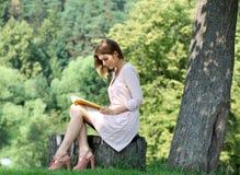 Muchacha rubia que lee un libro en el parque Imagenes de archivo