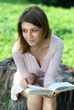 Muchacha rubia que lee un libro en el parque Imagen de archivo libre de regalías