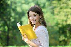 Muchacha rubia que lee un libro en el parque Imagen de archivo