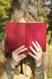 Muchacha rubia que lee un libro en un parque en un día soleado Imagen de archivo