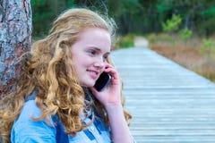Muchacha rubia que llama por teléfono al móvil en naturaleza Fotos de archivo libres de regalías