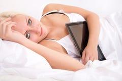 Muchacha rubia que miente de lado en la cama que sostiene una PC de la tableta Imagenes de archivo