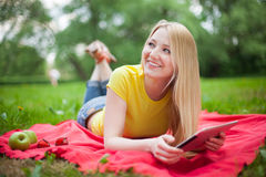 Muchacha rubia que miente en el parque con la tableta Fotografía de archivo