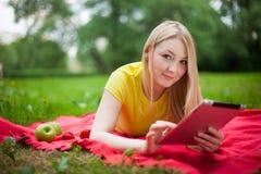 Muchacha rubia que miente en el parque con la tableta Foto de archivo