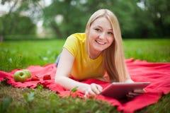 Muchacha rubia que miente en el parque con la tableta Imagen de archivo