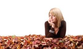 Muchacha rubia que miente en hojas de otoño coloreadas Imágenes de archivo libres de regalías