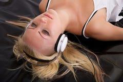 Muchacha rubia que miente en látex negro con los auriculares Imágenes de archivo libres de regalías