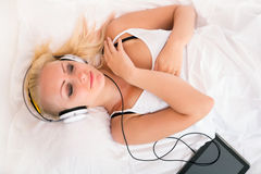 Muchacha rubia que miente en la cama que escucha la música Fotos de archivo