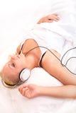Muchacha rubia que miente en la cama que escucha la música Imagen de archivo
