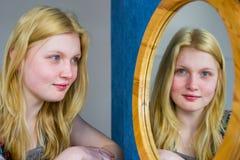 Muchacha rubia que mira en espejo Imagen de archivo libre de regalías