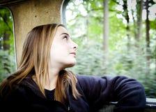 Muchacha rubia que mira fuera de una ventana del tren Imagen de archivo libre de regalías